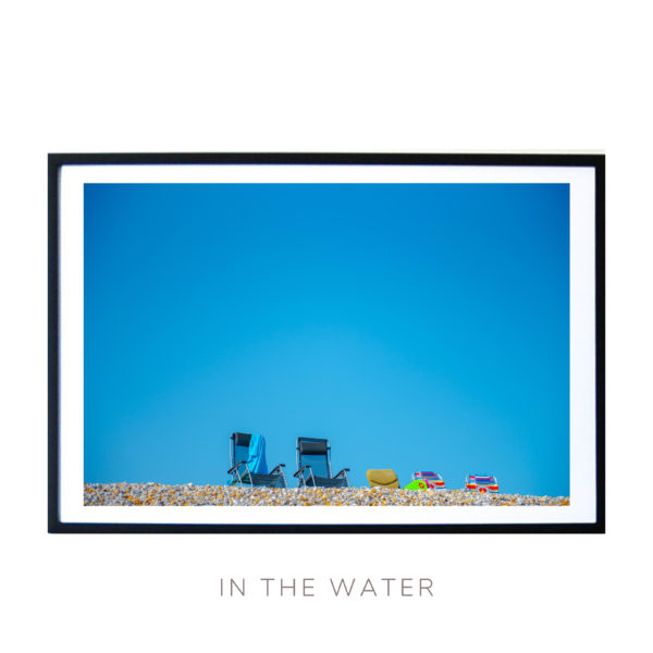 Wall Art featuring a blue sky beach chairs and pebbles on a sunny day in the UK