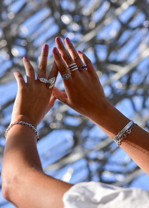 Photo of jewellery shot at Kew Gardens featuring silver rings in hand against the blue sky
